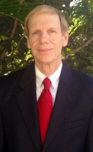 A headshot of Rod Reed. He is wearing a black suit jacket, a red tie and a white shirt.
